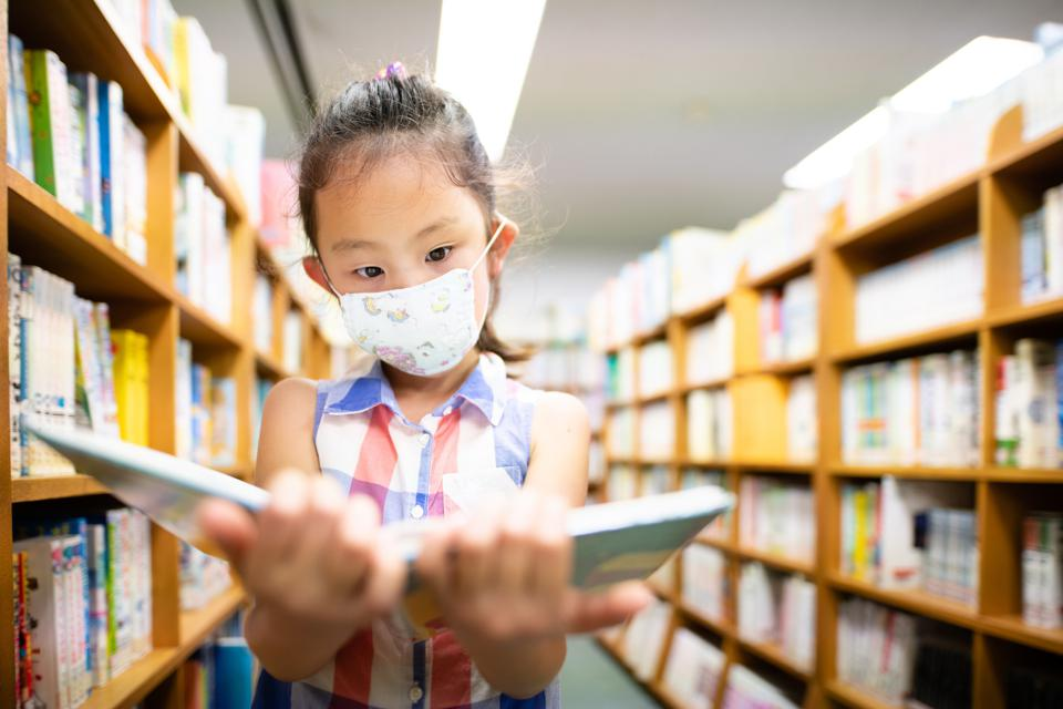 A young female student wearing a mask opens a book in a school library.