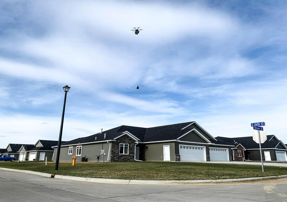 A Flytrex drone hovers above a suburban house and lowers a delivery package on a wire.