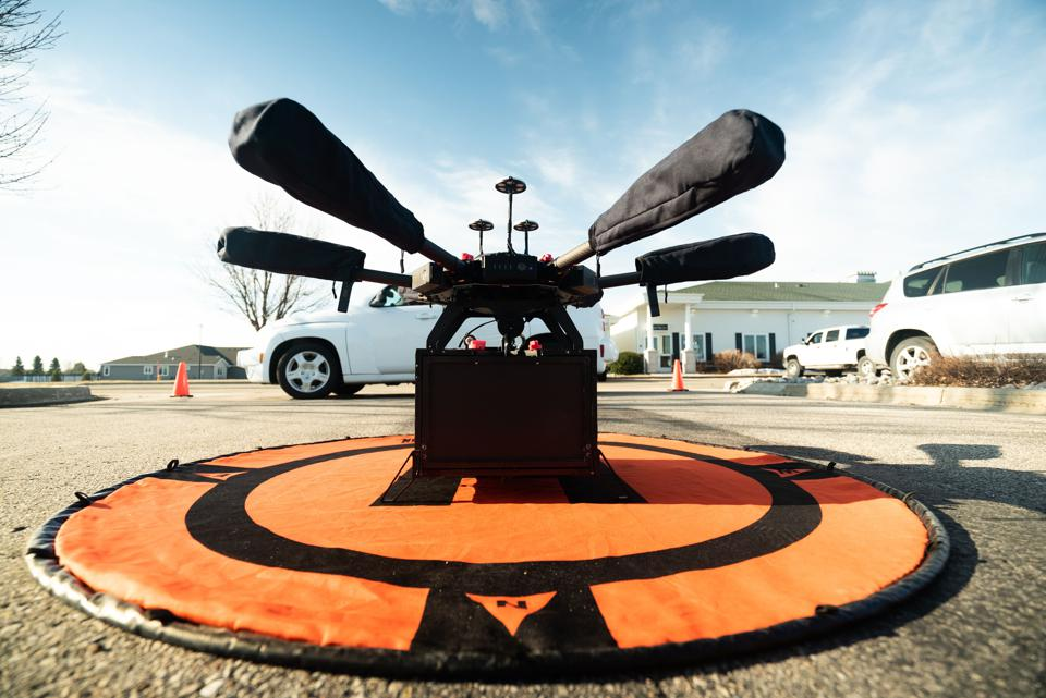A Flytrex delivery drone sits on a small take-off mat in a parking lot.