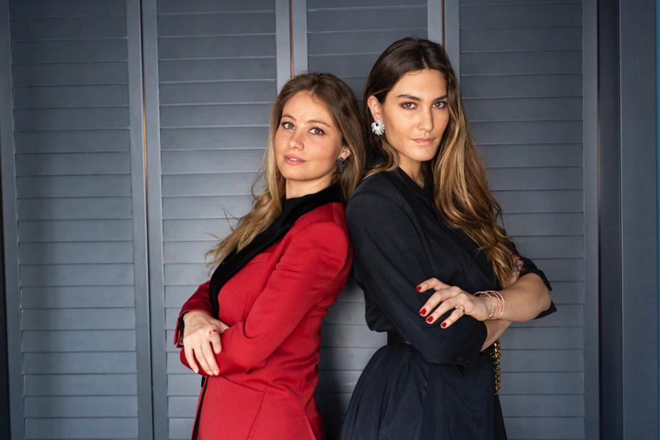 two brunette women stand next to each other, wearing red and black suits respectively
