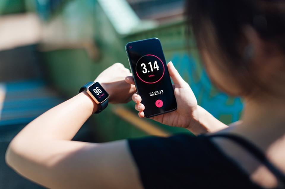 Young Woman Using Fitness App On Smart Phone And Smart Watch For Tracking Workout