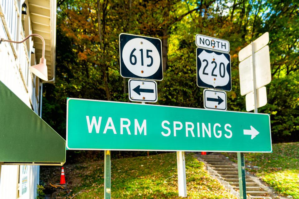 Hot Springs, USA downtown town village city in Virginia countryside with street road highway 615 and 220 directional sign for Warm Springs and arrow