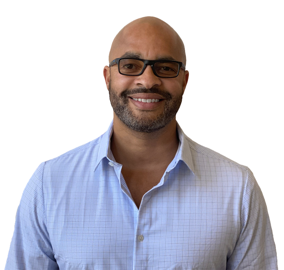 A bald Black man with a beard and glasses smiling into the camera wearing a blue button up shirt.
