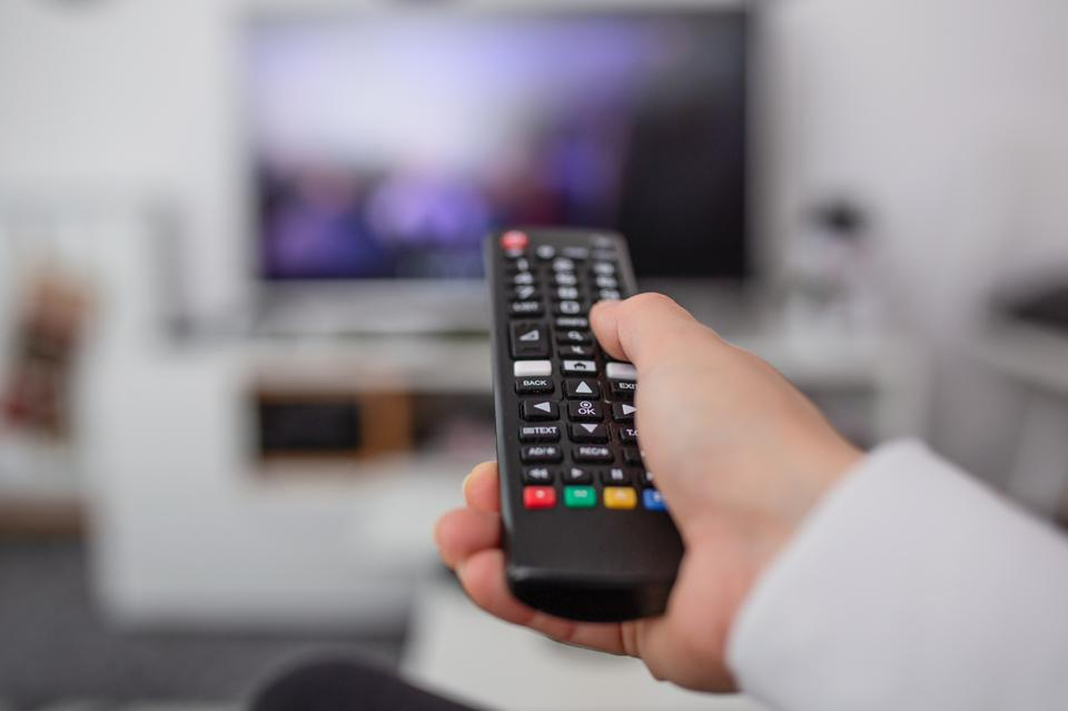 Watching TV and using remote controller. Hand with remote controller changing channels or opening apps on smart tv