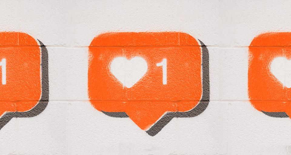 A white brick wall with Instagram's ″like″ notification spray painted onto it.