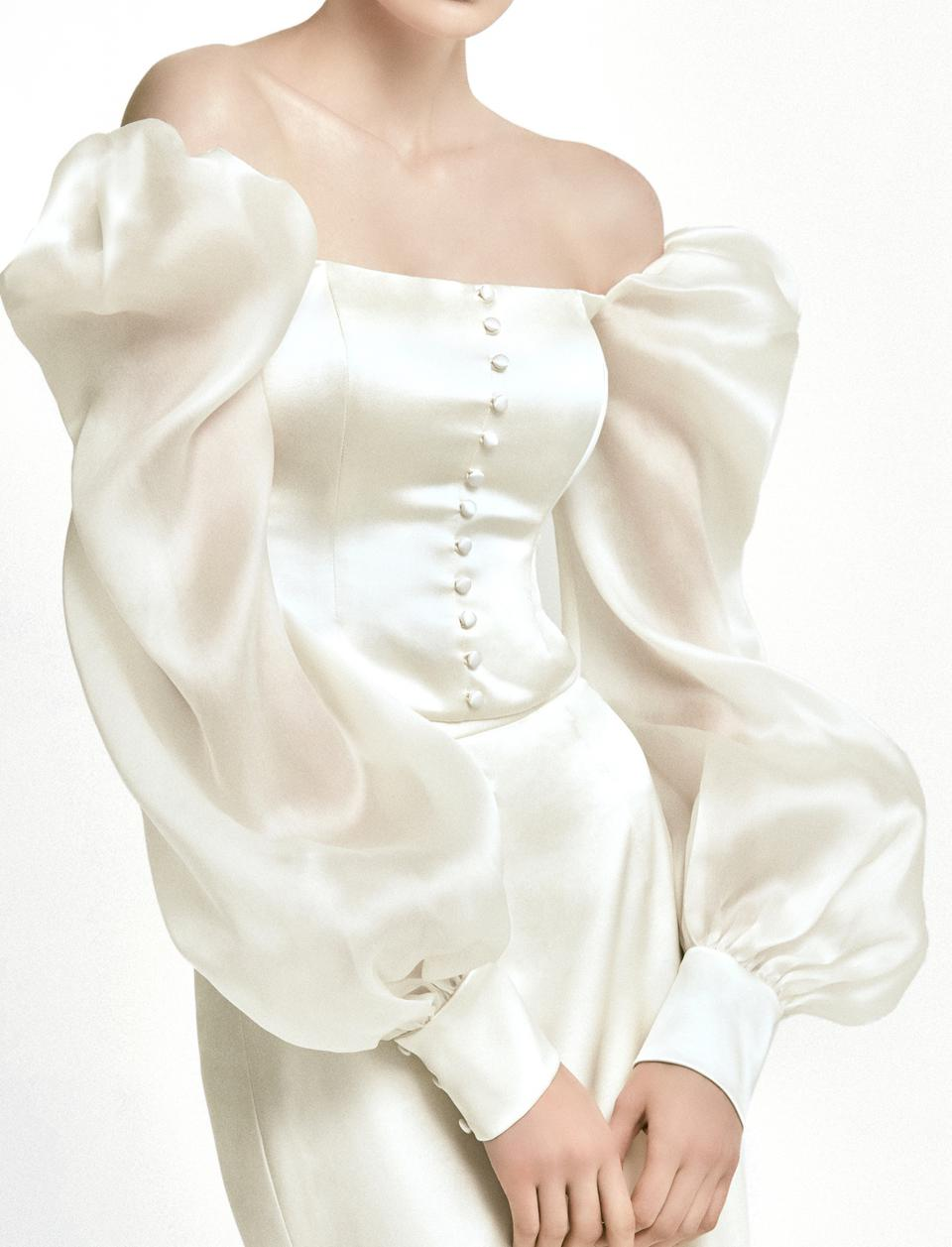 Ivan Young Silk Gazer Puffy Sleeves Satin Top is made with 100% silk and boasts a button appliqué along the front and zip closure in the back.