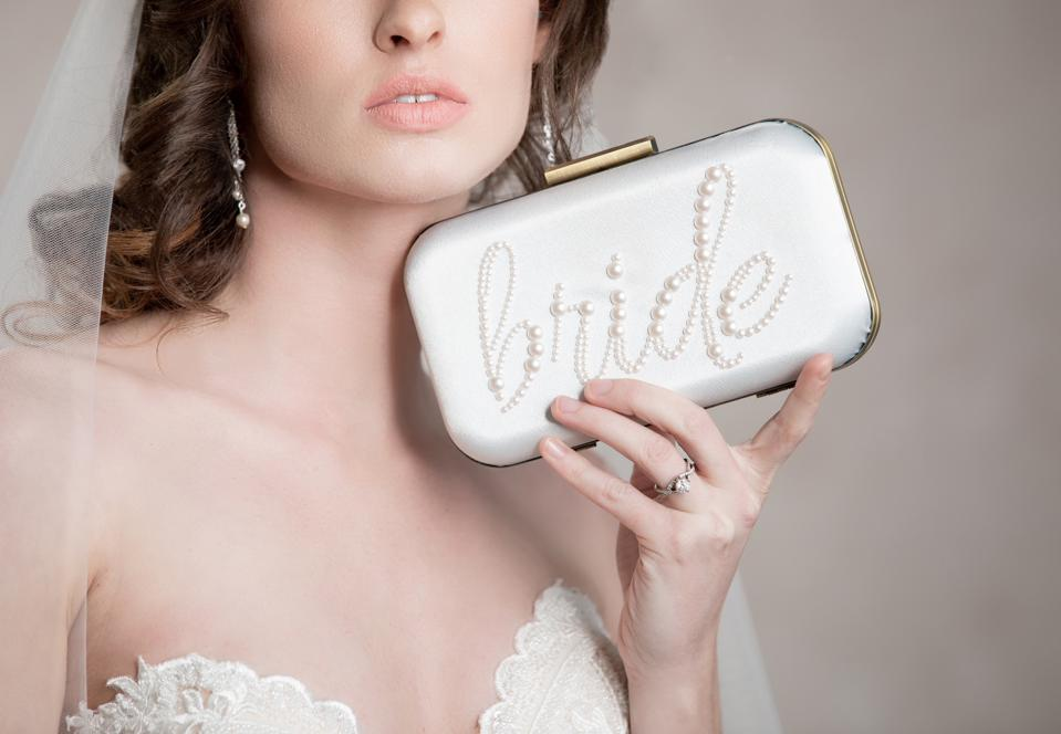 Ariel Taub's ″EVER AFTER″ clutch for the Bride is the perfect accessory for your engagement party, bridal shower and wedding day. Measuring 7.75 in. x 4.5 in., the Ever After clutch is available in select colors and embellishments to personalize and complete your wedding day style.