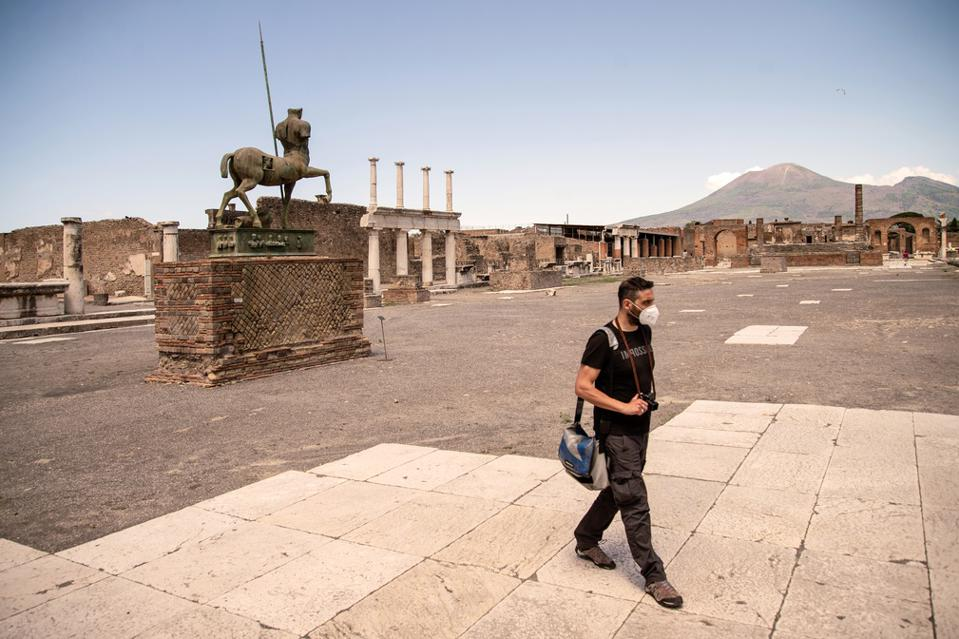 photographer walks in Pompeii Archaeological Park in Italy.