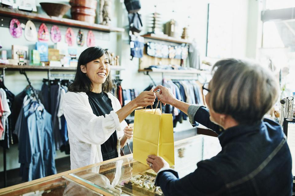 Shop owner handing bag to smiling client after shopping in clothing boutique