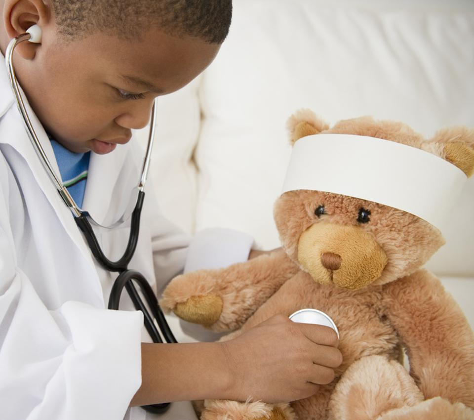 Boy playing doctor with teddy bear