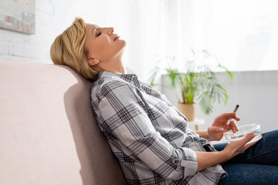 side view of mature woman with closed eyes sitting on sofa and holding joint with legal marijuana