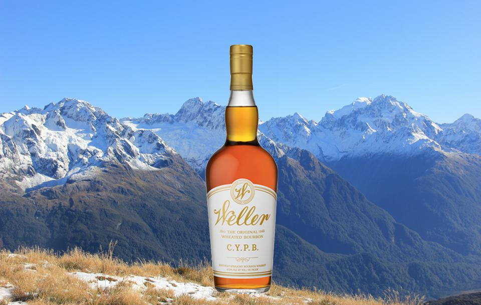 A bottle of white label bourbon in front of mountains in New Zealand