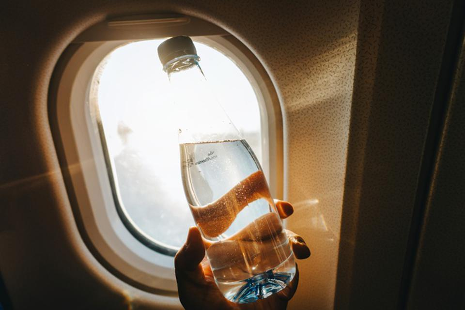 Cropped hand of woman holding a bottle of water against airplane window in front of golden sunbeam while travelling.