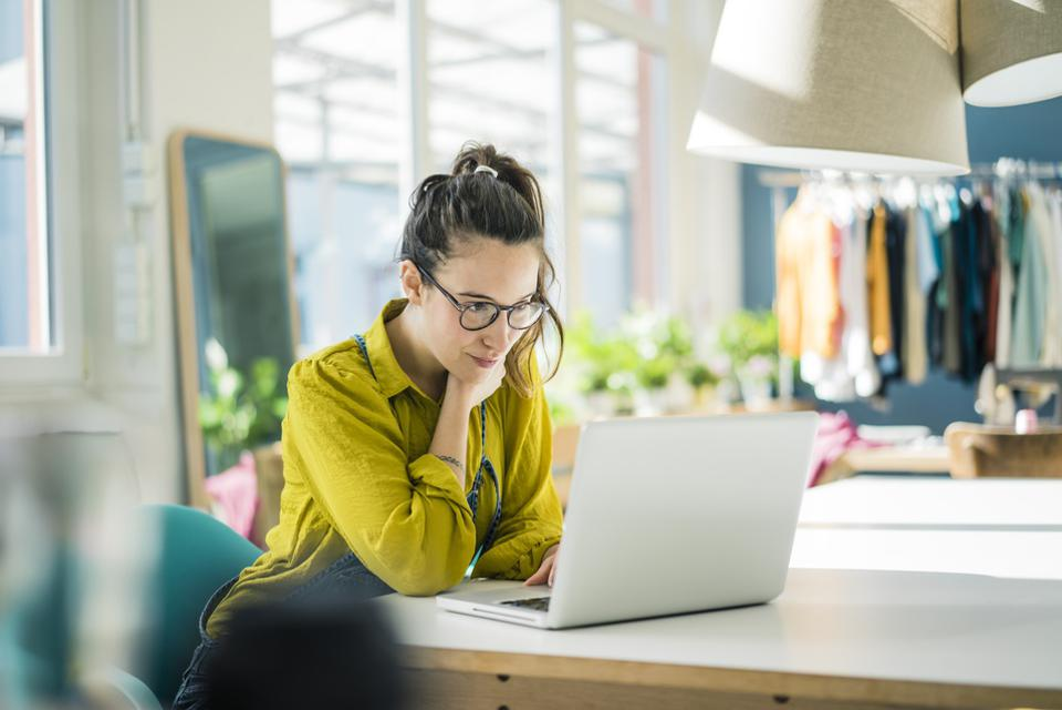 Fashion designer sitting at desk in her studio looking at laptop