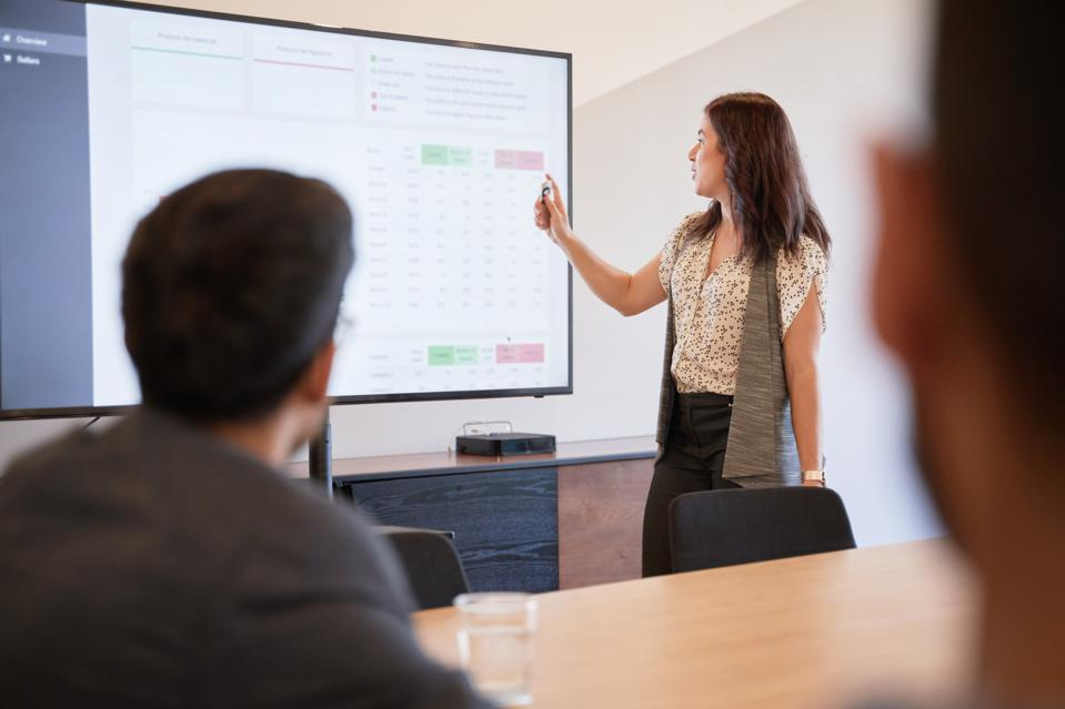 Businesswoman using graphs on screen in business meeting