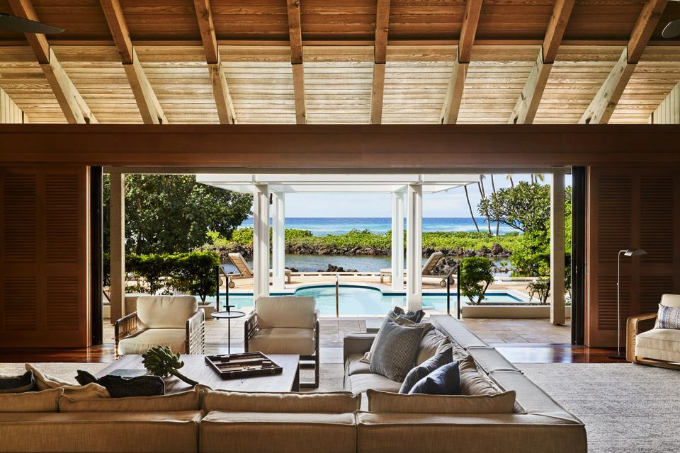An open living room overlooking a swimming pool and the Pacific.