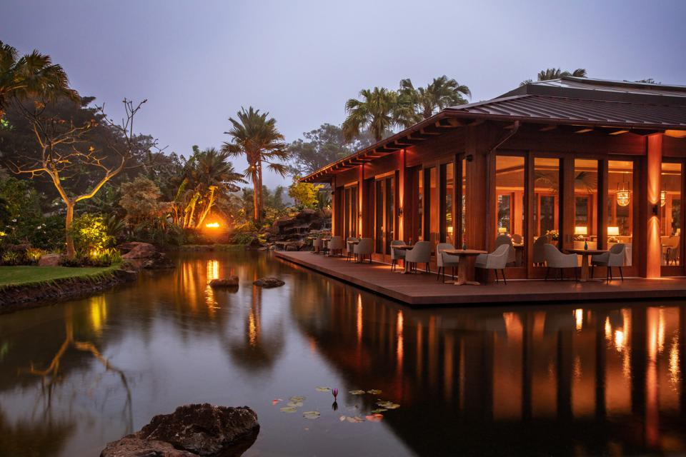 A wooden restaurant with floor-to-ceiling windows overlooking a pond at sunset