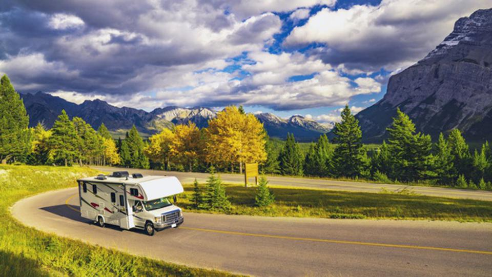 Recreational Vehicle Driving on Autumn Highway In Beautiful Mountains Wilderness