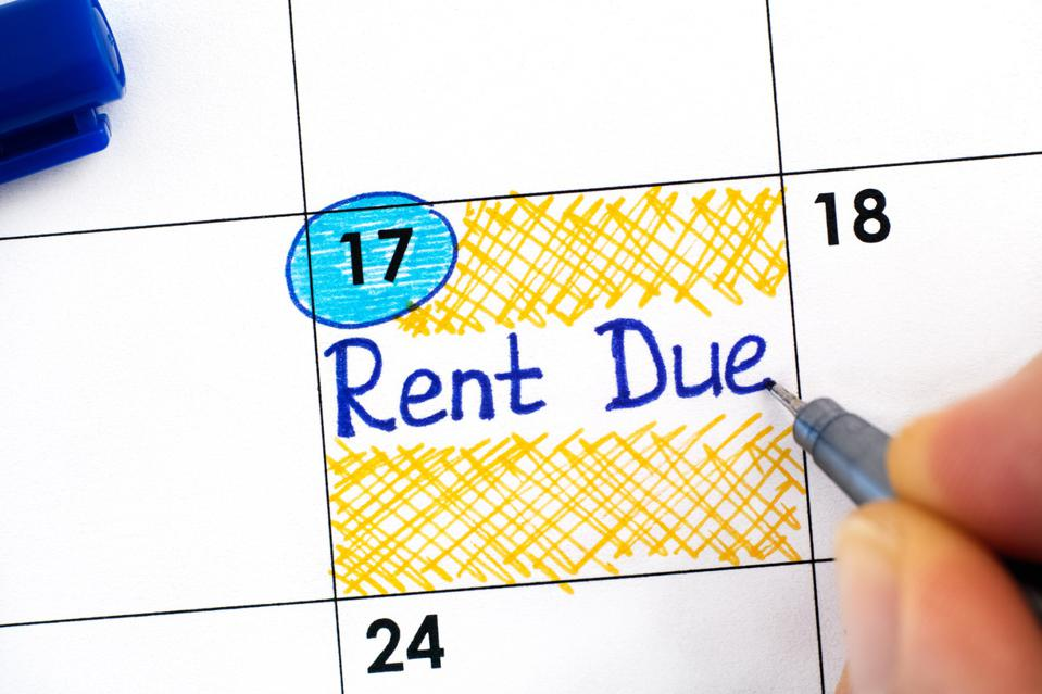 Woman fingers with blue pen writing reminder Rent Due in calendar.