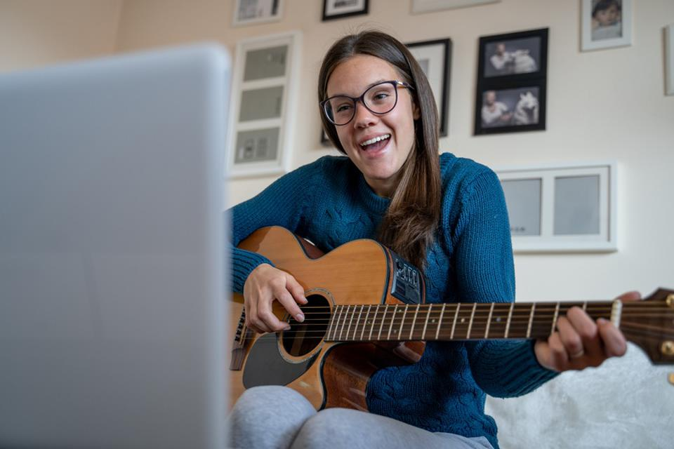 Young Woman Practicing Singing and Playing Guitar Following Online Course in Living Room - stock photo