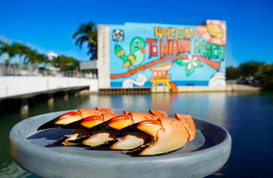 A plate of stone crabs held in front of a graffiti ″Welcome to Miami″ sign