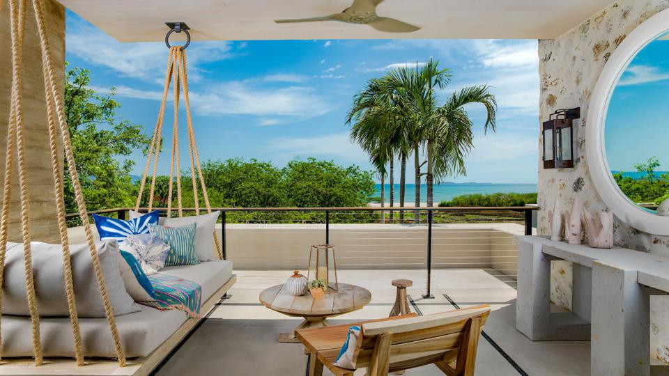 A hotel room with a swinging chair and a view of the beach