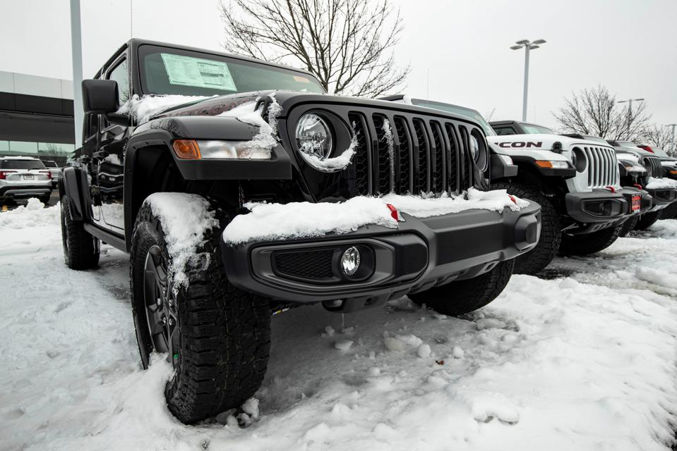 Jeep Wranglers parked outdoors on a snowy dealership lot.
