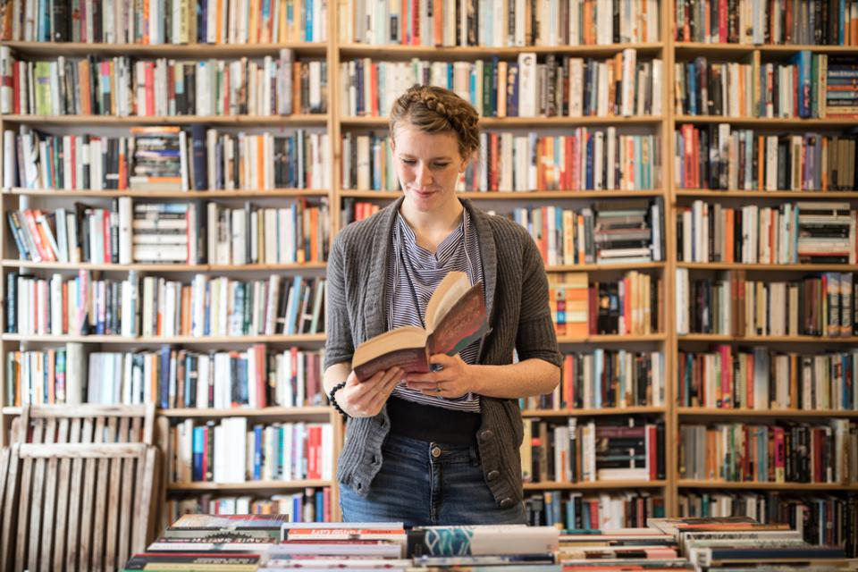 Beautiful young female customer reading book at bookstore