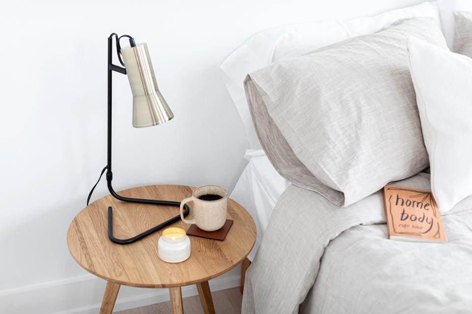 A bed with linen bedding next to a wood table with coffee and a lamp