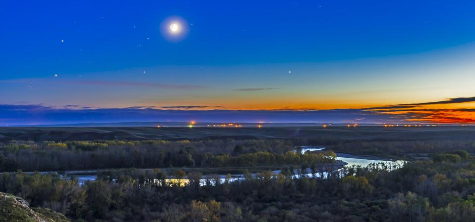 Moon with Antares, Mars and Saturn over Bow River in Alberta, Canada.