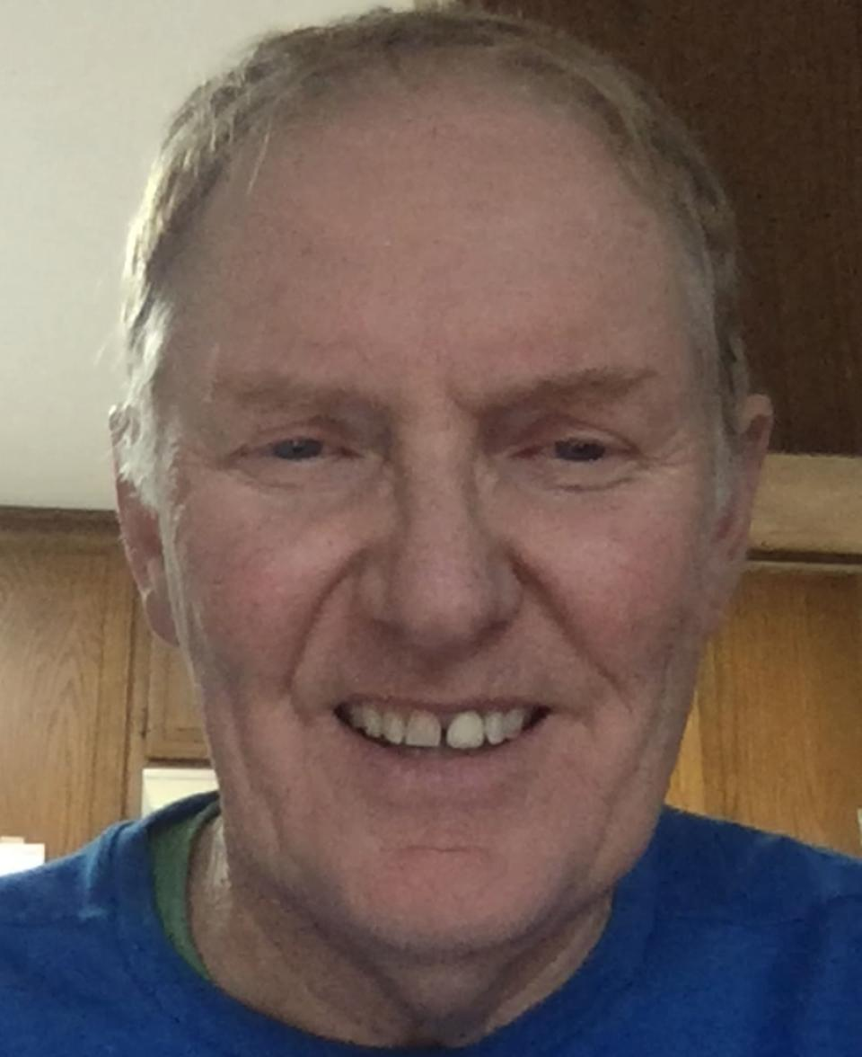 white man smiling, with blue shirt on