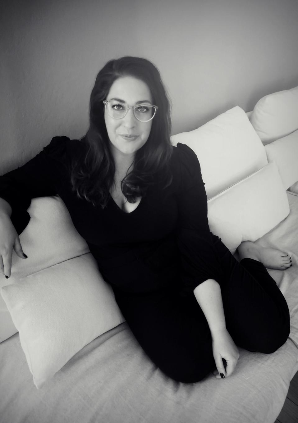Black and white headshot of Barker sitting on a sofa