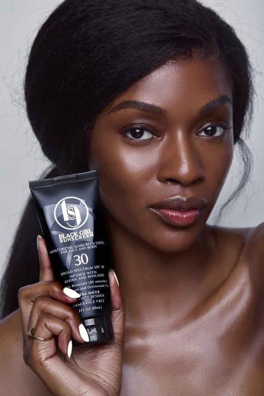 Model holding Black Girl Sunscreen bottle.