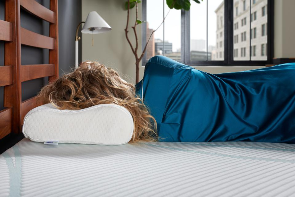 Back view of a woman sleeping on a TEMPUR-Neck Pillow.