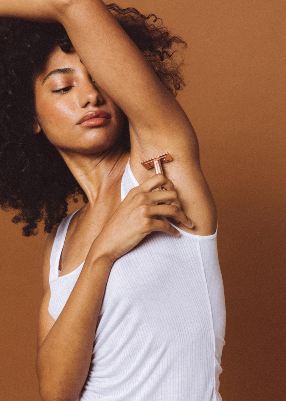 Model for Oui the People shaving armpit with metal razor.