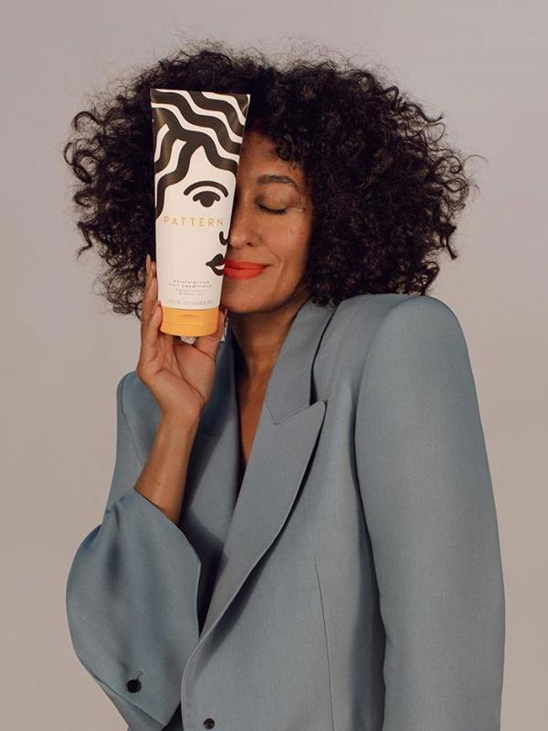 Tracee Ellis Ross with her pattern beauty deep conditioner bottle.