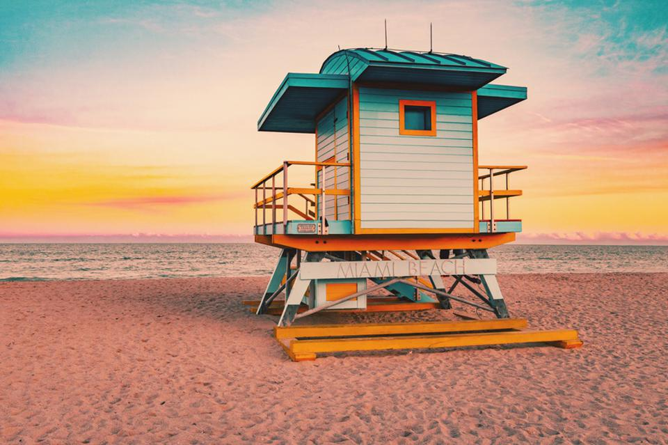 Colorful Miami Beach lifeguard tower with stunning sunset sky and empty beach.