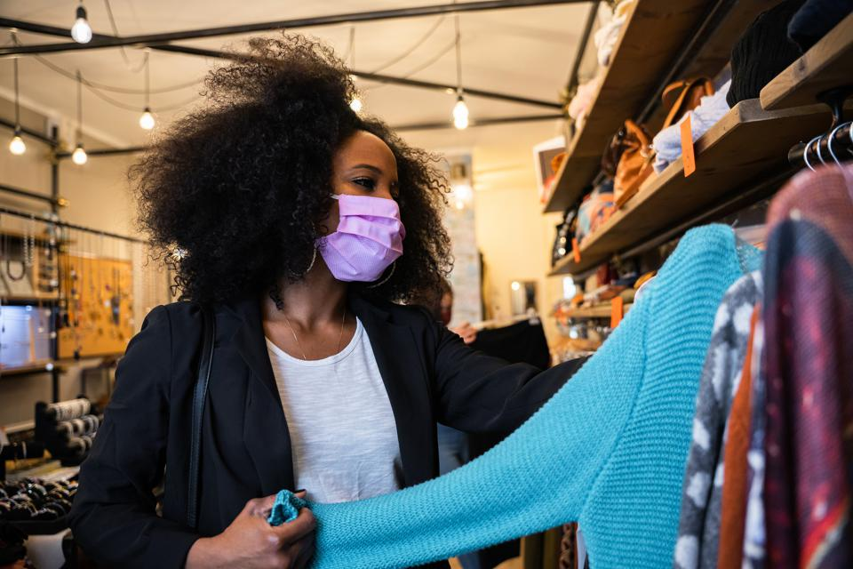 Customer in a clothing store wearing a protective mask and looking at a sweater for sale