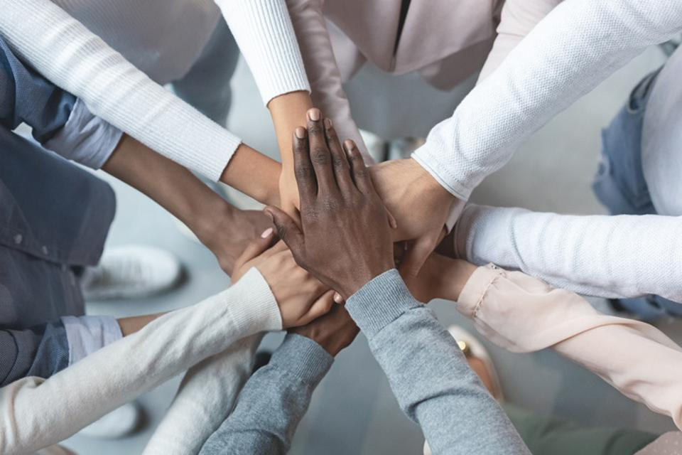International business team putting hands together in cooperation