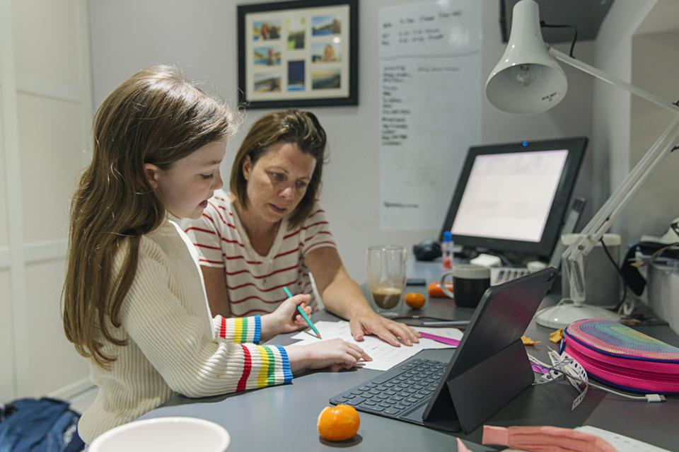 Woman helping daughter with her home schooling