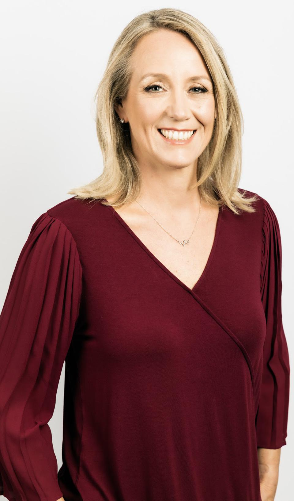 A white woman with blonde hair wearing a burgundy shirt.