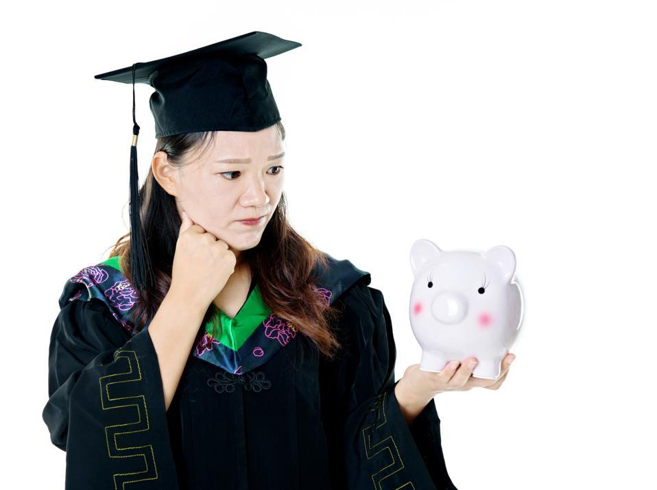 Female graduate holding a piggy bank