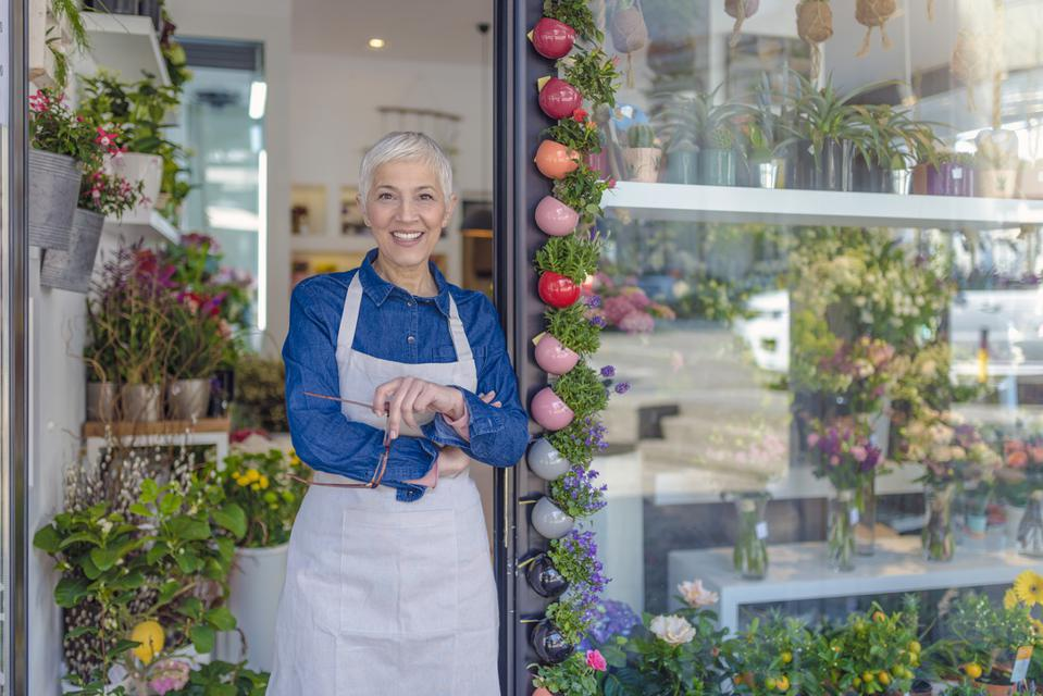 Photo of Beautiful mature woman standing in front of flower shop