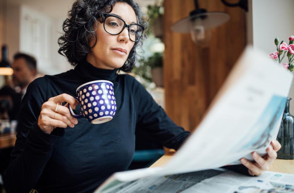 Businesswoman at cafe reading newspaper