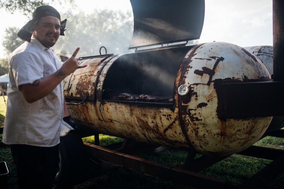 Chef in front of a large smoker.