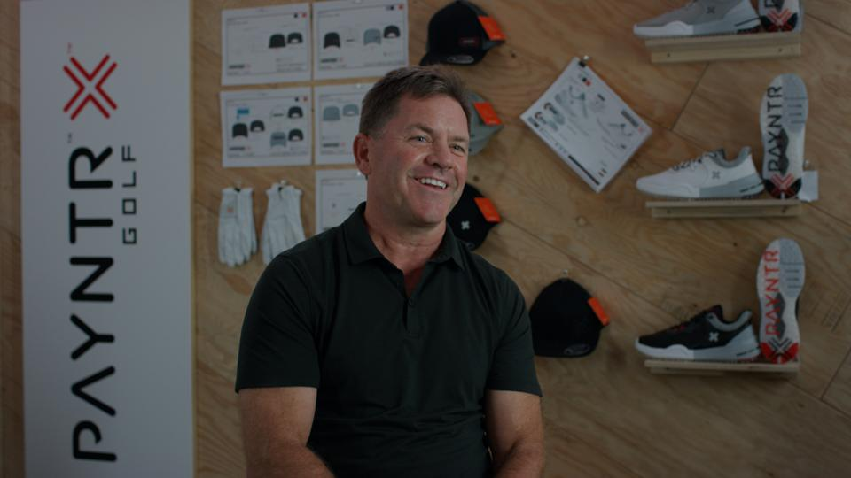 Mike Forsey, co-founder of Payntr Golf in front of a display of Payntr shoes.