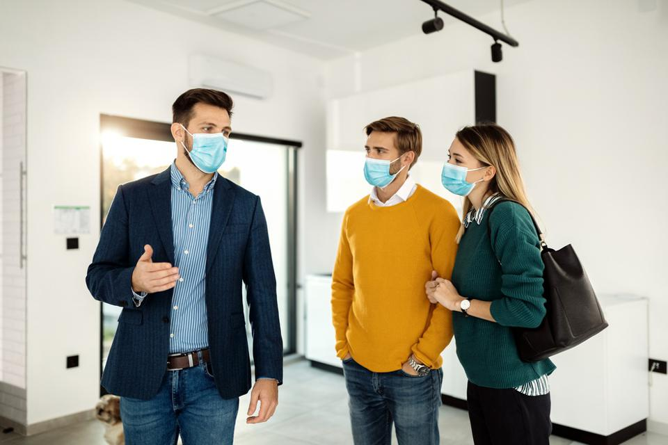 Real estate agent talking to a couple while showing them a new apartment during coronavirus pandemic.