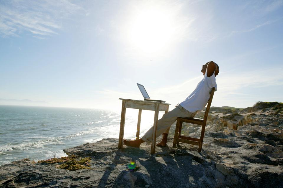 Man relaxing at his desk on seaside cliff