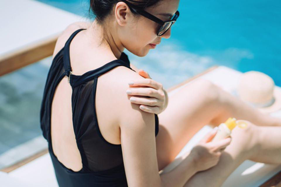 Young Asian woman applying suntan lotion while sunbathing by the swimming pool