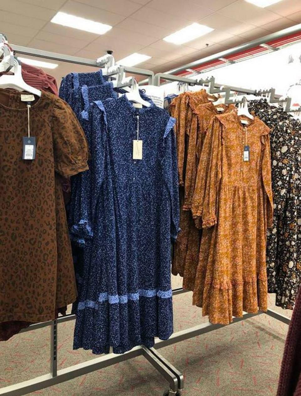 An in-store metal display rack at Target with four floral prairie dresses hanging on hangers.